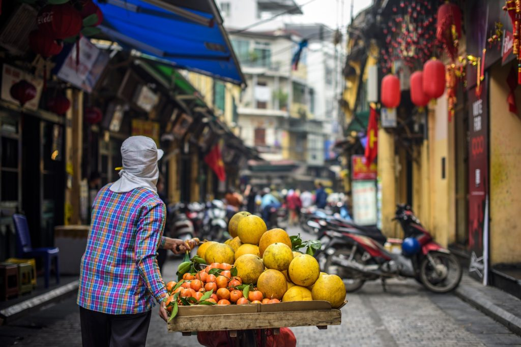 A man in Vietnam walking a fruit cart down the street.