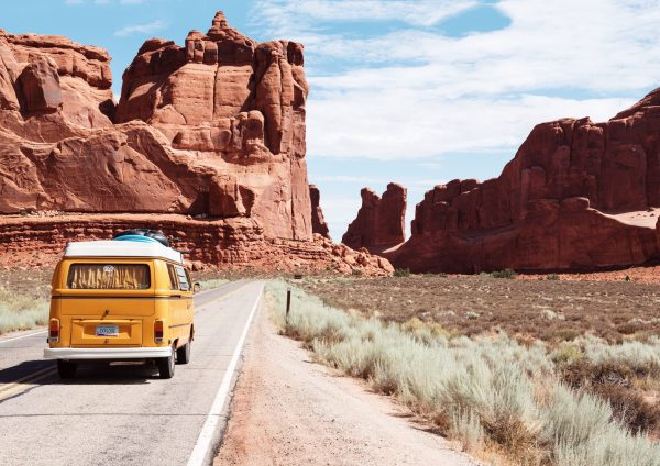 Vintage RV on a road trip with scenic outdoor view.